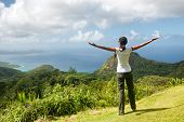 Young woman enjoying the view over rainforests towards the Indian Ocean from the Mission Lodge Lookout, Seychelles