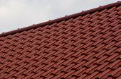 image of red roof tile  - House roof with red tiles on a cloudy day - JPG