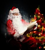 Christmas concept with Santa Claus in costume holding wish list. Christmas tree on background