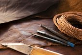 Leather craft. leather crafting tools and thread on a work table.