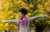 Cheerful Young Woman Standing Outdoors With Arms Outstretched