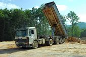 stock photo of truck-cabin  - big tipper truck unloading land on the site - JPG