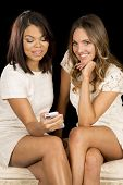 Two Women White Dresses Sit Phone One Smile