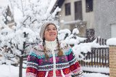 picture of snowball-fight  - Portrait of a happy young woman in the middle of a snowball fight on a snowy winter day