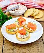 Crackers with cream and salmon in plate on board