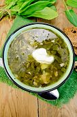 Soup green of sorrel and spinach with sour cream on board