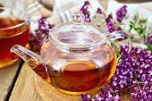 Tea of oregano in glass teapot on board with napkin