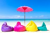 colorful pillows and bright umbrella on tropical sea and beach background, vacation in tropics