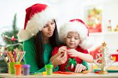 mother and kid daughter in Santa hats making christmas tree of plasticine
