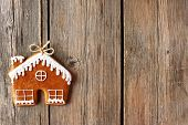 Christmas homemade gingerbread house cookie over wooden background