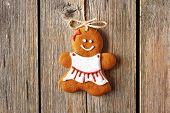 Christmas homemade gingerbread girl over wooden background