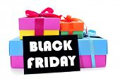 a pile of gift boxes of different colors and a black signboard with the text black friday written in white, on a white background