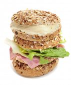 two brown bagels topped with different seeds, such as sesame and poppy seeds, one filled with ham and lettuce mix and another one filled with spreadable cheese on a white background