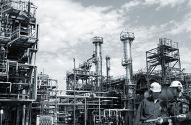 foto of refinery  - two refinery workers with large industrial refinery in background - JPG