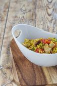 foto of curry chicken  - Bowl with curry flavored rice chicken and vegetables on rustic wooden table