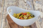 image of curry chicken  - Bowl with curry flavored rice chicken and vegetables on rustic wooden table