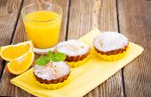 stock photo of bakeshop  - Homemade Muffins Ready for Breakfast with orange slices and juice on a wooden background - JPG