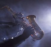 picture of saxophone player  - African American jazz musician playing the saxophone through smokey light in club