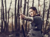 stock photo of archer  - Medieval archer woman she wearing a chainmail and use a bow and arrow gloomy forest cross - JPG
