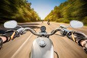 image of biker  - Biker driving a motorcycle rides along the asphalt road - JPG