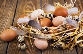 stock photo of manger  - Speckled quail eggs and chicken eggs in the manger on a rustic background - JPG