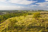 stock photo of slag  - View from a slag heap over flat west German landscape near Aachen with lots of wind turbines and some clouds on blue sky - JPG