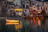 stock photo of old boat  - old boat drifting in a harbor of Cefalu at dusk Sicily - JPG