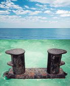 image of bollard  - Old black rusted bollard mounted on green ship deck with sea landscape on a background - JPG