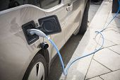 foto of electric station  - Charging an electric car at a roadside urban charging station showing a close up of the attached connector and cable in a green energy concept