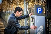 stock photo of dispenser  - Young man waiting for a parking ticket to be dispensed from the ticket booth at the side of a street after making his payment - JPG