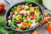 stock photo of lenten  - Mixed vegetables in retro frying pan and ingredients on wooden rustic table - JPG