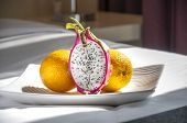 picture of fruit platter  - Sliced dragon fruit with whole oranges - JPG