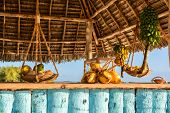 stock photo of roping  - In the picture beach bar in Nungwi ( Zanzibar ) at sunset with exposed coconut banana and tropical fruit .This bar is made with cane bamboowooden and straw rope.
