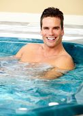 stock photo of hot-tub  - Young man relaxing in hot tub - JPG