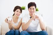 stock photo of sofa  - happy Young asian couple relaxing in sofa - JPG