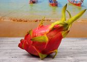 foto of dragon fruit  - dragon fruit on a wood table top on the beach - JPG