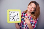 stock photo of late 20s  - Happy young woman holding big clock and pointing finger on it over gray background - JPG