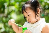 foto of blowers  - Little girl playing bubble blower at outdoor - JPG