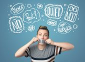 stock photo of taboo  - Young woman with taped mouth and white drawn thought clouds around her head - JPG