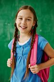 picture of schoolgirls  - Cheerful schoolgirl with backpack looking at camera - JPG
