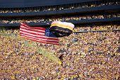 Us Airborne Parachutist Travels Past The Crowd At The Um-msu Game