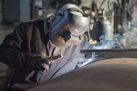 stock photo of pipe-welding  - welder brews manual arc welding a workpiece of large diameter pipe - JPG