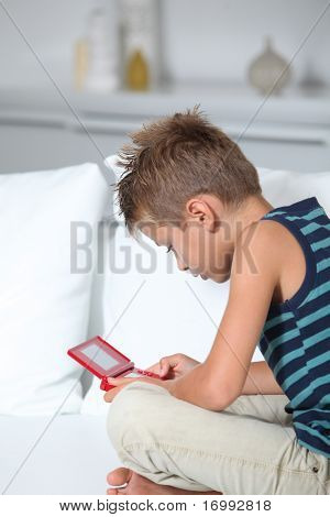 poster of Little boy playing video games on sofa
