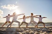 fitness, sport, yoga and healthy lifestyle concept - group of people making warrior pose on beach poster