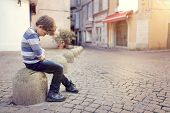Upset problem child sitting on a street corner concept for bullying, depression, child protection or poster