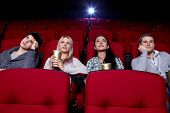 stock photo of watching movie  - Satisfied girls and bored boys watching a movie at the cinema - JPG