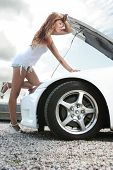 beautiful young woman repairing the car