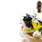 A bottle of olive oil and olives over white