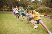 Children pulling a rope in tug of war in the park poster