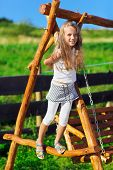Cute Little Girl With Blond Long Hair Playing On Wooden Chain Swing In Rural Playground